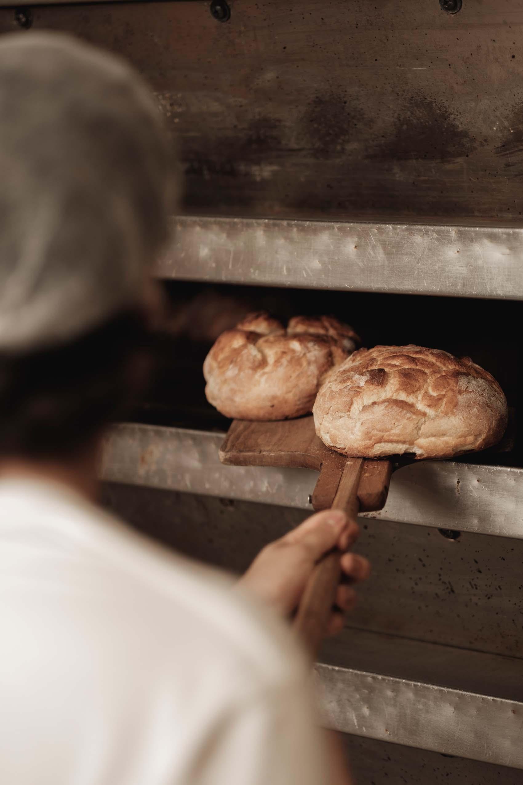 Blick über die Schulter eines Bäckers: Frisches Brot aus dem Ofen der Konditorei Brommler Memmingen